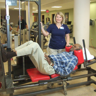 Female physical therapist helping patient on leg exercise machine.