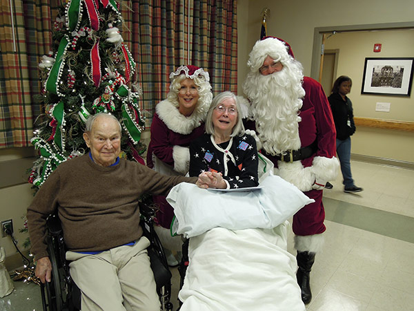 Santa and Mrs. Claus posing with senior patients
