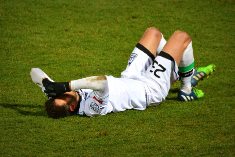 man, soccer player, injury, laying on field