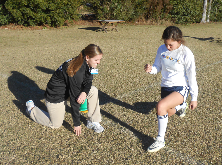 Athletic Trainer help female student athlete lunge.