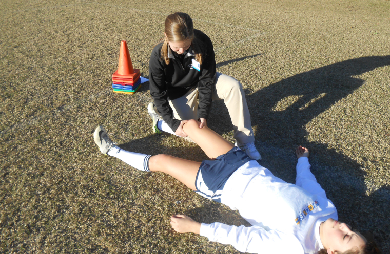 Athletic trainer evaluates a possible ACL tear on student athlete.