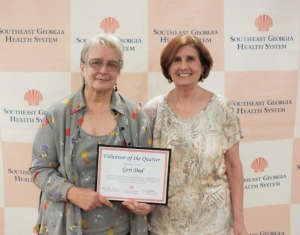 Two women posing with certificate recognizing SGHS volunteers