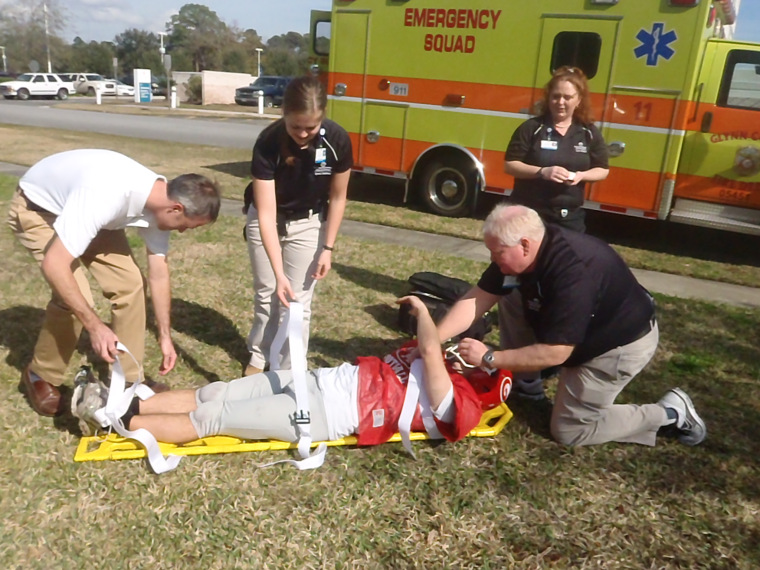 EMTs strap football player to stretcher.