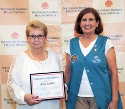 Two women pose with a certificate celebrating SGHS volunteers