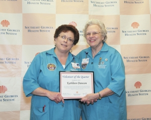 Two women posing with a certificate that recognizes SGHS volunteers