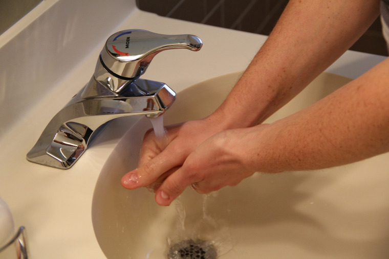 Hands being washed at sink