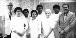 Diverse group of hospital workers posing for a shot in celebration of the opening of The Radiation Oncology Center in 1990